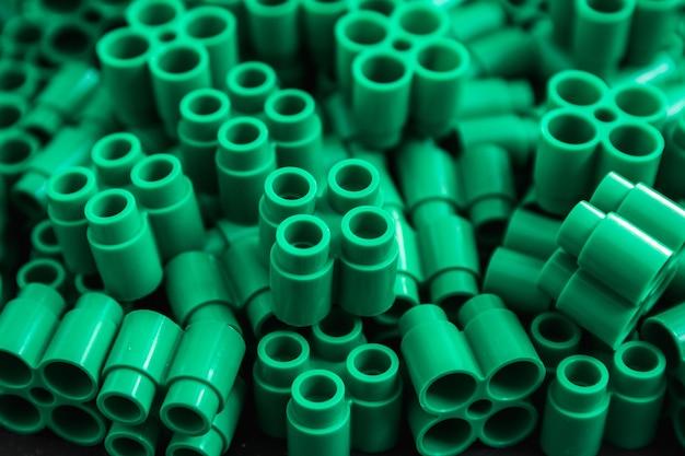 Grüne plastiksteine und details von spielzeug. grüner hintergrund. nahaufnahme.