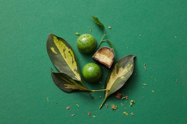 Grüne pralinen mit schönen blättern auf dem grünen tisch