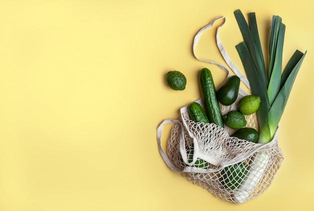 Grüne produkte in einem wiederverwendbaren netzbeutel auf gelbem grund