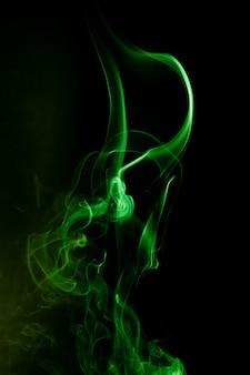 Grüne rauchbewegung auf schwarzem hintergrund.