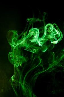 Grüne rauchbewegung auf schwarzem.