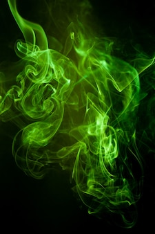Grüne rauchbewegung auf schwarzer oberfläche.