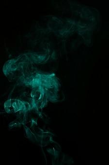 Grüne rauchfahne gewellt wirbelt auf schwarzem hintergrund