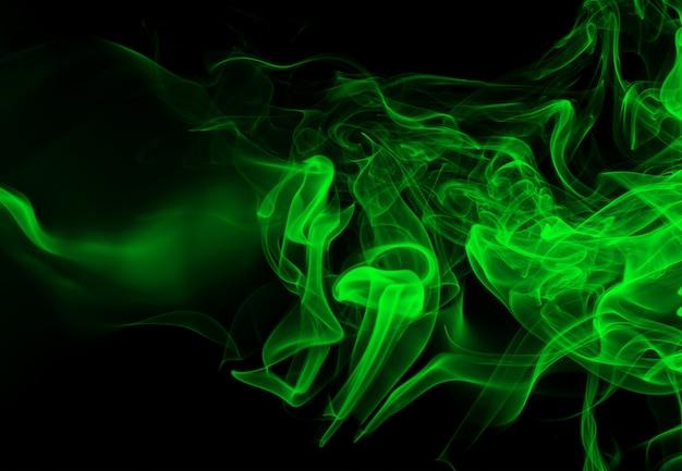 Grüne rauchzusammenfassung auf schwarzem backgroud, dunkelheitskonzept