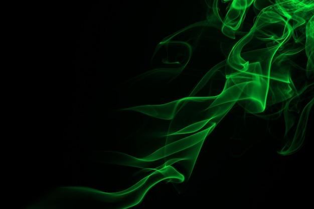 Grüne rauchzusammenfassung auf schwarzem hintergrund, dunkelheitskonzept
