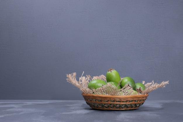 Grüne, reife feijoa auf korb auf marmor.
