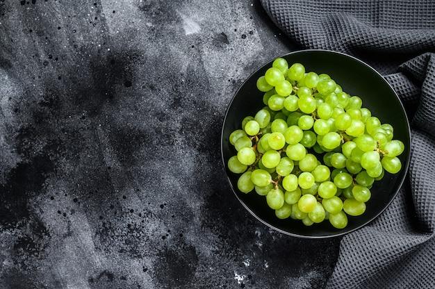 Grüne reife trauben in einem teller, früchte des herbstes. schwarzer hintergrund