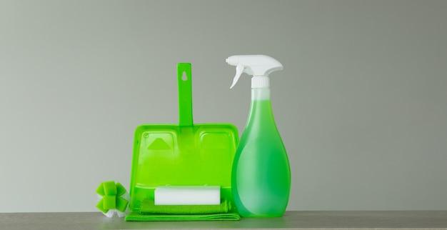 Grüne reihe von reinigungsmitteln und werkzeugen für den frühjahrsputz.