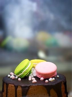 Grüne rosa macarons verzieren auf schokoladenkuchen