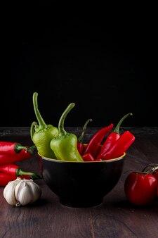 Grüne rote peperoni in der keramikschale knoblauch und paprika