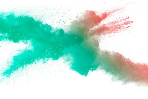 Grüne rote staubpartikelexplosion auf weißem hintergrund. farbpulver staub spritzen.
