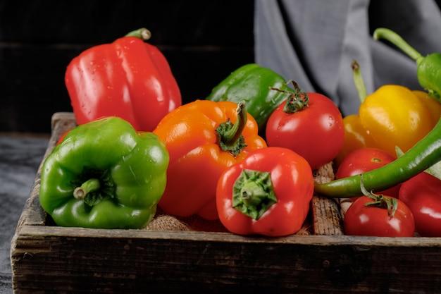 Grüne, rote und gelbe paprika in einem holztablett.