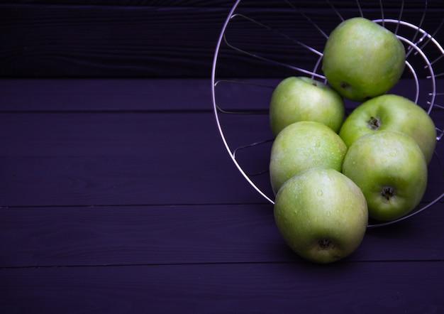 Grüne saftige äpfel mit wasser fällt auf dunklen hintergrund. freier exemplarplatz.