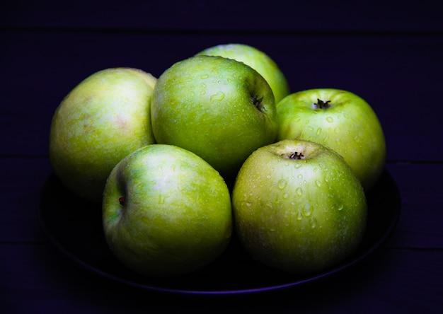 Grüne saftige äpfel mit wasser fällt auf schwarzblech auf dunklem hintergrund.