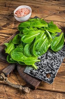 Grüne salatblätter des baby romain auf hölzernem schneidebrett. hölzerner hintergrund. draufsicht.