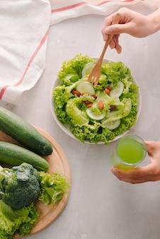 Grüne salatschüssel mit gemüse auf küchentisch, ausgewogene ernährung die