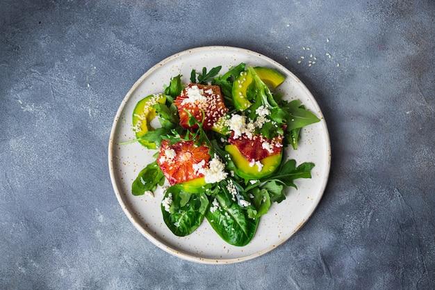 Grüne salatschüssel mit rucola, mangold, avocado, blutorange, meersame, hüttenkäse auf keramikplatte auf blauem steinhintergrund. konzept für gesunde ernährung. flatlay mit copyspace. nahansicht