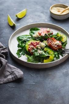 Grüne salatschüssel mit rucola, mangold, avocado, blutorange, meersame, hüttenkäse auf keramikplatte auf blauer steinmauer mit limette, serviette und gabel und messer. konzept für gesunde ernährung.