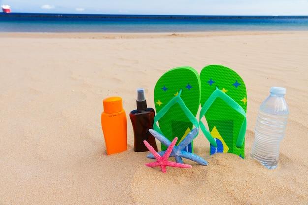 Grüne sandalen, eine flasche wasser und sonnencreme am sandstrand am meer