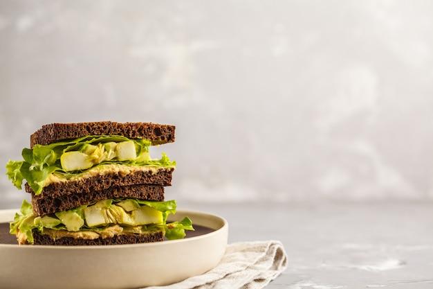 Grüne sandwiches des strengen vegetariers mit hummus, gebackenem gemüse und avocado, kopienraum.