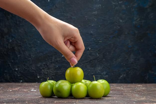 Grüne sauerkirschpflaumen der draufsicht, die weich und frisch auf der hölzernen rustikalen hintergrundfrau ausgekleidet sind, nehmen eine davon fruchtfarbe sauer weich