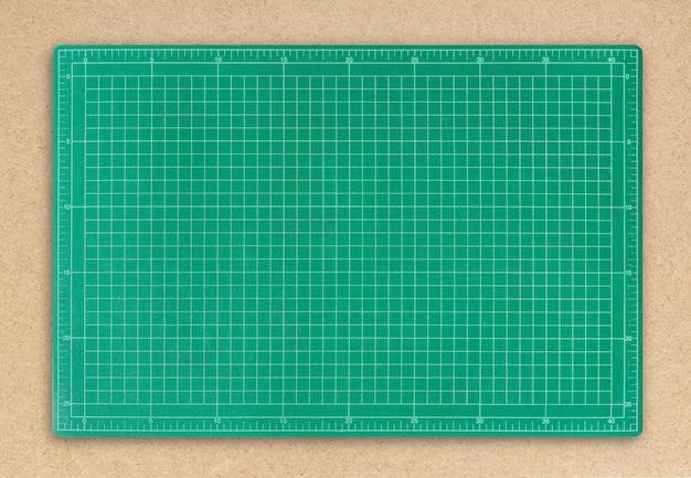 Grüne schneidematte auf hintergrund des braunen papiers.