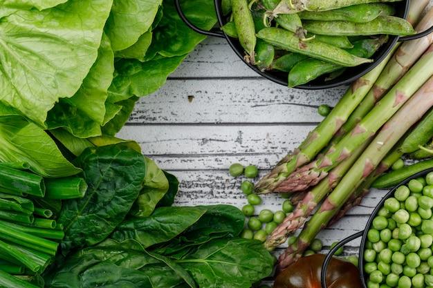Grüne schoten, erbsen mit tomaten, sauerampfer, spargel, frühlingszwiebeln, salat in töpfen auf holzwand, flach liegen.