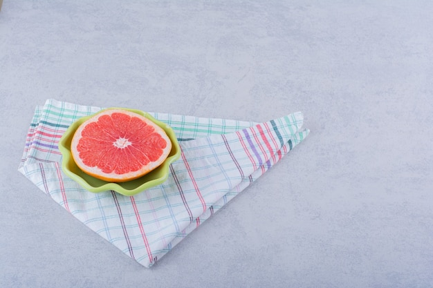 Grüne schüssel mit frischer grapefruitscheibe auf stein.