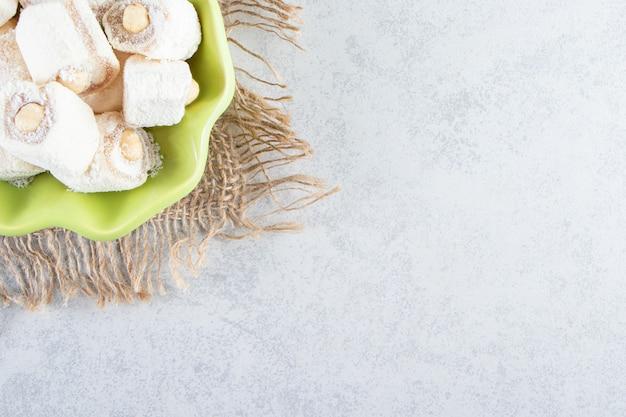 Grüne schüssel mit köstlichen leckereien mit nüssen auf stein.