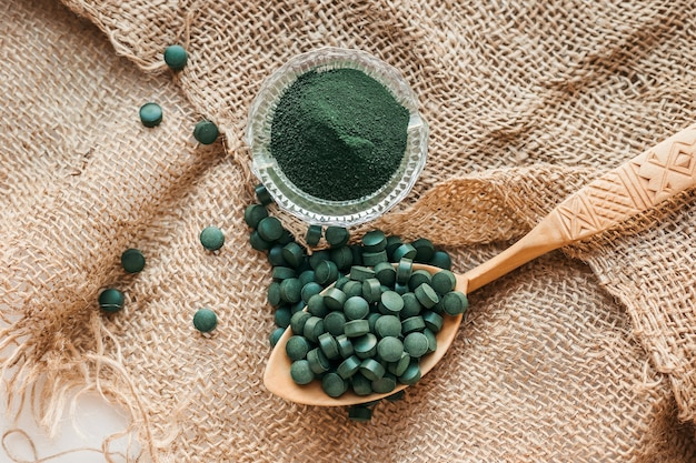 Grüne seetangspirulina in den tabletten und im pulver auf einem sackleinenhintergrund. draufsicht