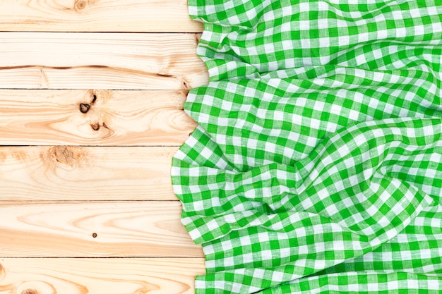 Grüne serviette auf holztisch, draufsicht