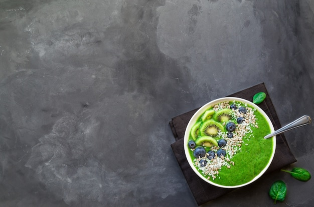 Grüne smoothie-schüssel des frühstücks mit kiwi-blaubeeren und sonnenblumenkernen auf grauem betonhintergrund