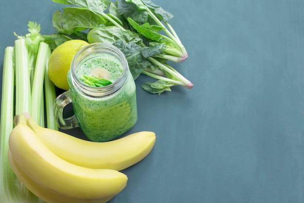 Grüne smoothies und seine komponenten in einer glasschale auf einem getonten hintergrund