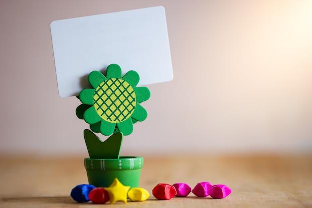 Grüne sonnenblume des klipphalterkartenstandplatzes formte und mehrfarbige papiersterne auf holztisch.