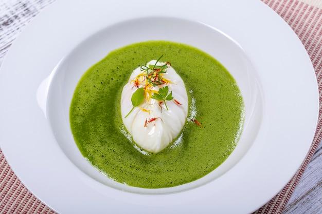 Grüne soße mit pochiertem ei in weißem teller