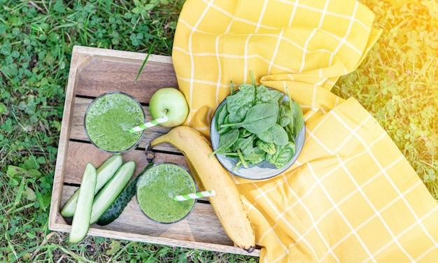 Grüne spinat-smoothies mit früchten, banane, apfel, gurke