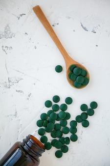 Grüne spirulina-pillen fielen aus der flasche. mehrere pillen in einem holzlöffel. super food konzept. spirulina nahrungsergänzungsmittel.