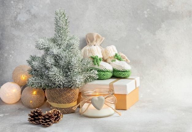 Grüne stiefeletten für ein neugeborenes mit kerzengeschenkkastengirlande und weihnachtsbaum