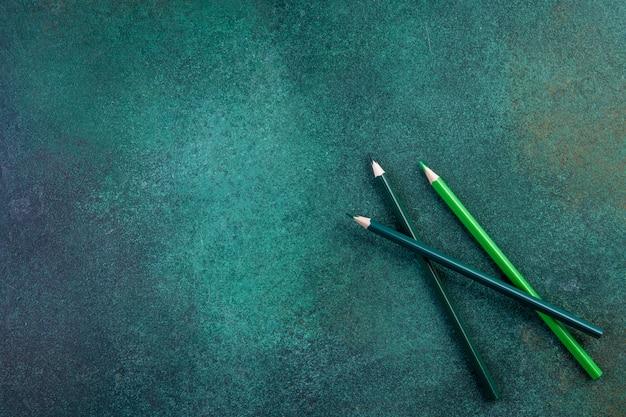 Grüne stifte des kopierraums der draufsicht auf einem grünen hintergrund