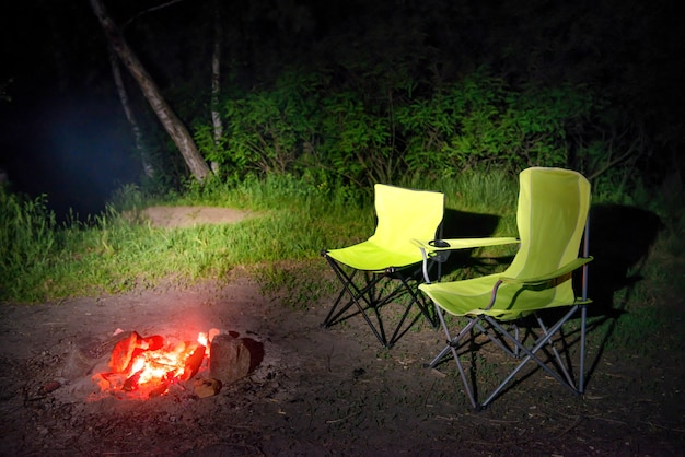 Grüne stühle in der nähe von lagerfeuer nachts. kamin im camping