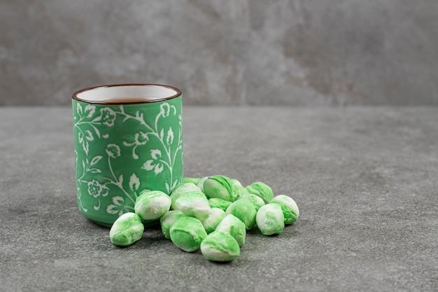 Grüne süße bonbons mit einer tasse leckerem tee