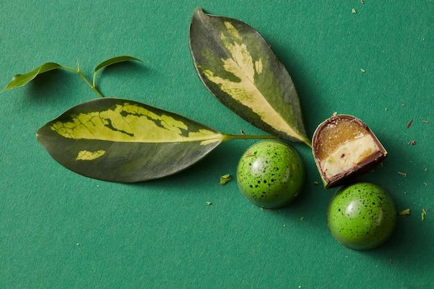 Grüne süßigkeit mit grünen blättern auf einem grünen tisch