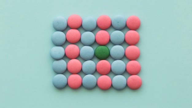 Grüne süßigkeit vereinbarte in den rosa und blauen süßigkeiten auf farbigem hintergrund