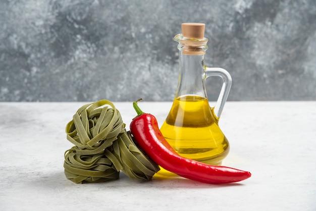 Grüne tagliatelle, roter pfeffer und olivenöl auf marmorhintergrund.