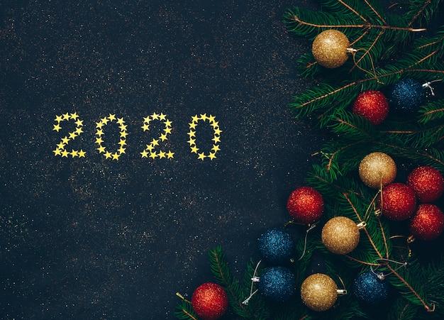 Grüne tanne mit weihnachtsdekoration und schwarzem hintergrund des neuen jahres
