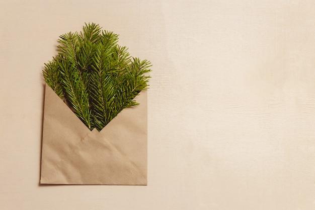 Grüne tannenbaumaste der draufsicht im braunen handwerksumschlag
