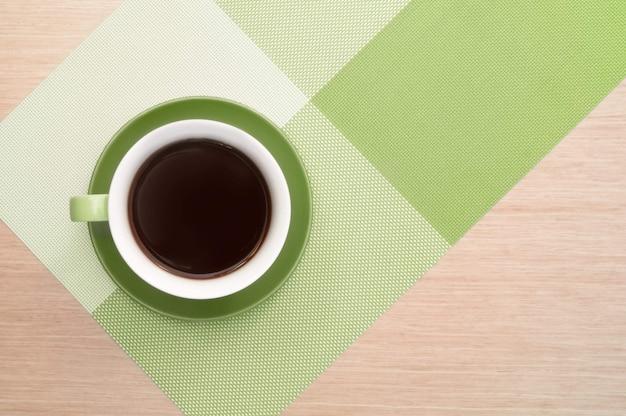 Grüne tasse kaffee auf dem hintergrund des rosa holztischs und der tischdecke. ansicht von oben