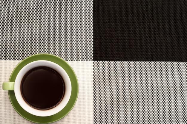 Grüne tasse kaffee auf schwarzem und weißem hintergrund der tischdecke. büro