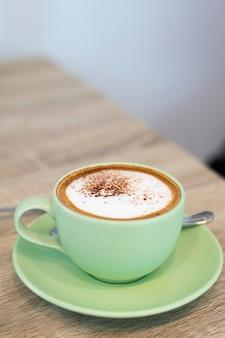 Grüne tasse kaffee latte auf holzuntergrund nahaufnahme