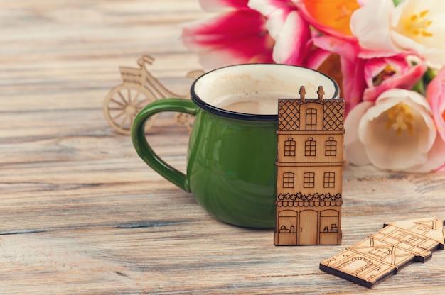 Grüne tasse kaffee, tulpen und spielzeugholzhäuser
